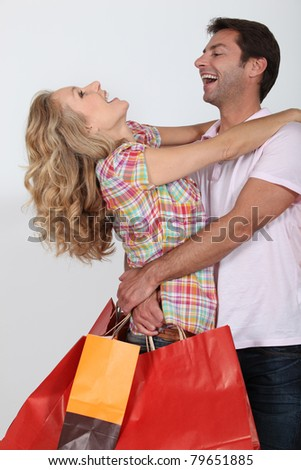 An elated couple embracing after a shopping spree.