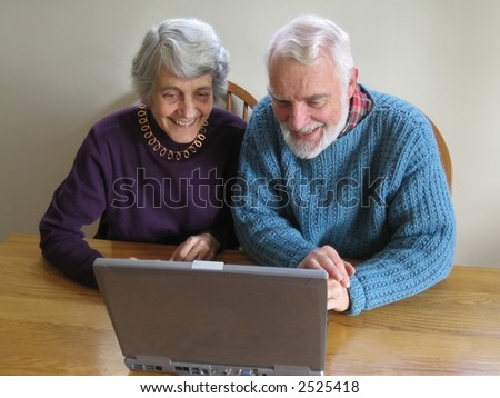 an elder couple looks at a laptop together