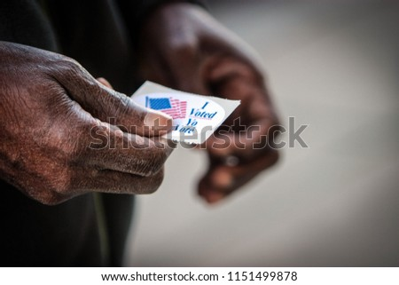 "An elderly African American man holds his ""I voted"" sticker after he cast his ballot in Washington, DC."