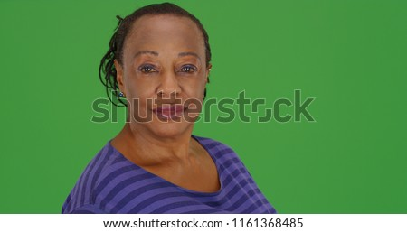 An elderly African American woman poses for a portrait on green screen stock photo