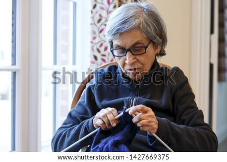 An elderly Asian Indian woman in UK sits knitting a blue jumper. Depicts seniors engaged in a hobby or activity