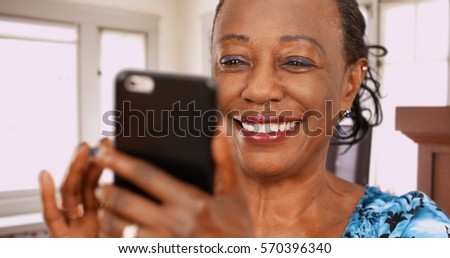 An elderly back woman swipes on her favorite dating app
