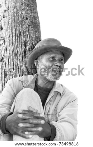 An elderly black man with a scruffy gray beard relaxes at a park on a sunny day.