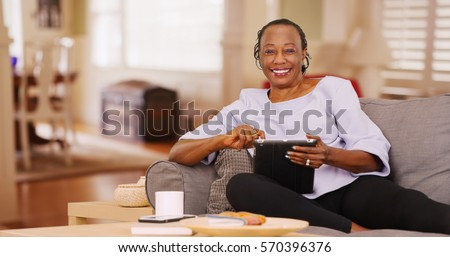 An elderly black woman happily uses her tablet while looking at the camera stock photo