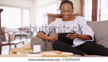 An elderly black woman uses her tablet while relaxing on the couch stock photo