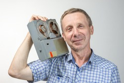 An elderly, blue-eyed, contented man listens to music on an old reel-to-reel tape recorder on a light background