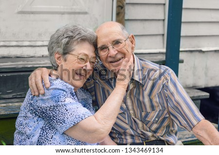 An elderly couple is sitting down on a May afternoon in Delcambre, Louisiana.  Two caucasian senior citizens are embracing each other. A marriage of an Octogenarian and Nonagenarian laughing in love.
