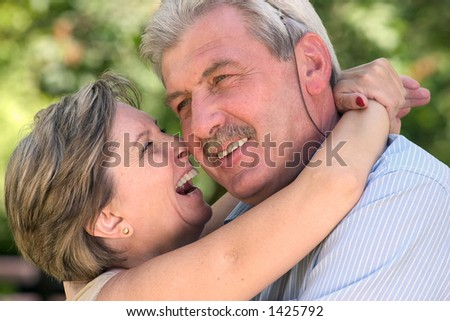 An elderly couple lauging a lot.