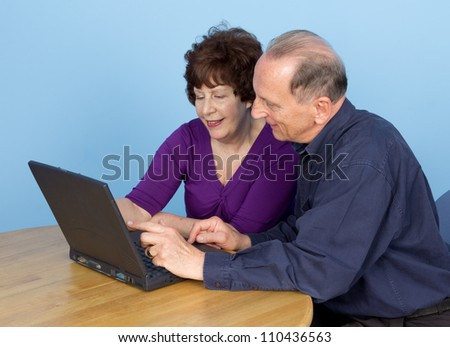 An elderly couple sitting down at a table looking at and using a laptop.