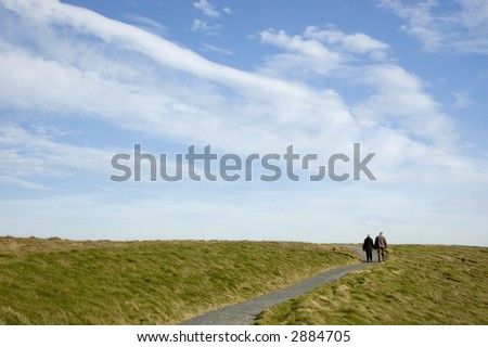 An elderly couple walking on a path to a big sky