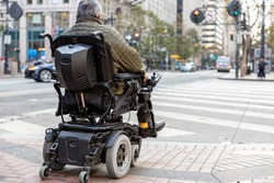 An elderly disabled person on an electric wheelchair on a city street in front of a pedestrian crossing. The concept of modern technology for people with disabilities.