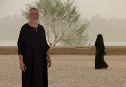 An elderly Egyptian in a black caftan is standing by a wide gravel path and looking into the camera. A woman in a black robe walks in the background. The Nile can be seen in the mist behind it.