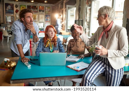 An elderly female boss discussing a project with her young colleagues in a relaxed atmosphere at office. Employees, office, work