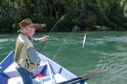 An elderly fisherman reels in a rainbow trout from his drift boat on Oregon's Mckenzie River near Eugene.