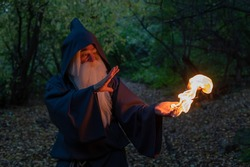 An elderly gray-haired witcher casts a fire spell in the forest. Man in wizard costume