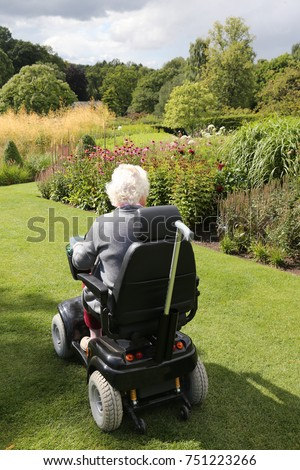 An elderly lady using a motor scooter to look around a garden #751223266