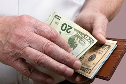 An elderly man counts the bills in his wallet. The concept of pension, salary, income and expenses.