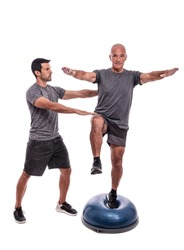 An elderly man doing a balance exercise, on one leg, on a hemisphere ball. With help of a fitness trainer. On a white isolated background.