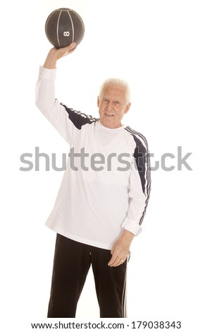 an elderly man holding up his weighted medicine ball.