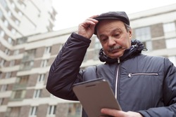 An elderly man in a cap is lost in the city and is looking for a way in the tablet