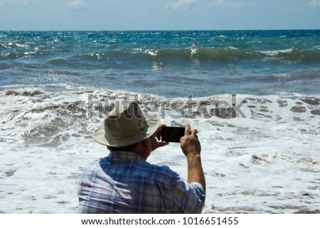 An elderly man in a plaid shirt and panama photographs the stormy sea on the phone. Old man takes a picture on the phone of a storm at sea on a sunny day. Blurred morsel background