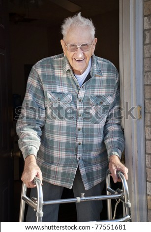 An elderly man in his nineties with a walker standing in his apartment door