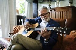 An elderly man is playing guitar