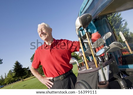An elderly man is standing next to a golf cart on a golf course.  He is smiling and looking away from the camera.  Horizontally framed shot.