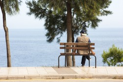 An elderly man sits on a bench by the sea and looks into the distance