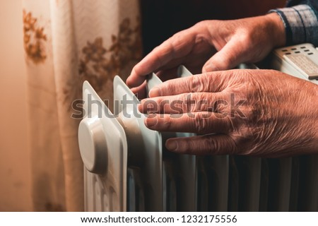 An elderly man warms his hands over an electric heater. In the off-season, central heating is delayed, so people have to buy additional heaters to keep houses warm despite increased electricity bills.