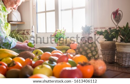 An elderly man washes a green apple under the jet of water. In the foreground an assortment of freshly picked healthy fresh fruit. Bright light from the window. One senior people