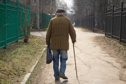 An elderly man with a stick is walking down the street. A man aged. The old grandfather is walking. The life of pensioners in Russia. Old age in the fall.