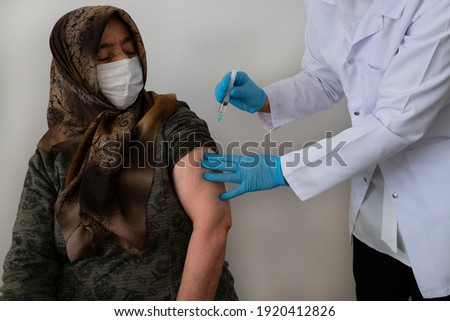 An elderly Muslim hijab woman who received a coronavirus vaccine injection by a doctor or nurse to get antibodies vaccinated the population. side effects, people at risk, antibodies, 2021 covid-19 65+