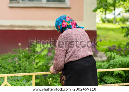 An elderly old lady in Russia. Pensioner on the street. An old woman in a headscarf. Russian life of an ordinary grandmother. Walking the old lady in the street.