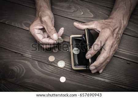 An elderly person holds the coins over the old empty wallet. The concept of poverty in retirement. #657690943