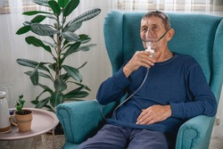 An elderly senior sits in a armchair with an oxygen mask in quarantine at home