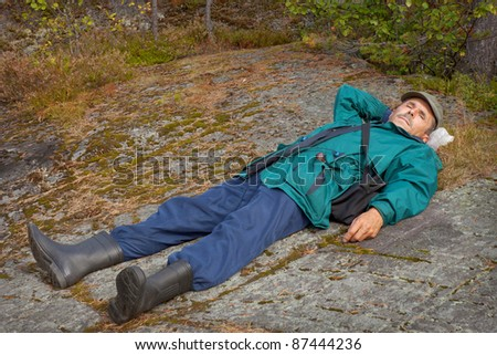 An elderly tourist resting lying on the rock