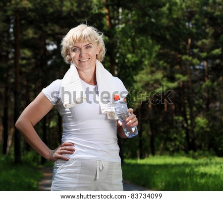 An elderly woman after exercising in the forest holding a bottle of water