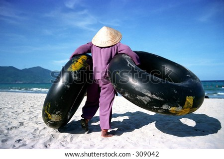 http://image.shutterstock.com/display_pic_with_logo/3053/3053,1114866672,1/stock-photo-an-elderly-woman-carries-inflated-tractor-tyres-on-china-beach-in-vietnam-309042.jpg