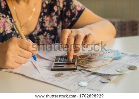 an elderly woman considers payments for utility bills; on a calculator, she considers payment for an apartment with money in Russian rubles; banknotes of 2000,100 rubles and Russian coins