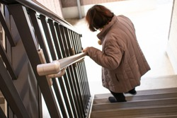 An elderly woman holding a railing and going down the stairs.