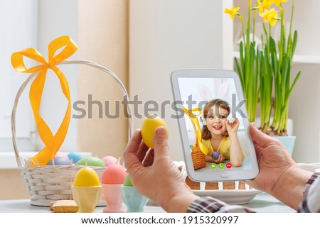 An elderly woman holds a digital tablet and talks to her granddaughter via video link during the Holy Easter holiday.