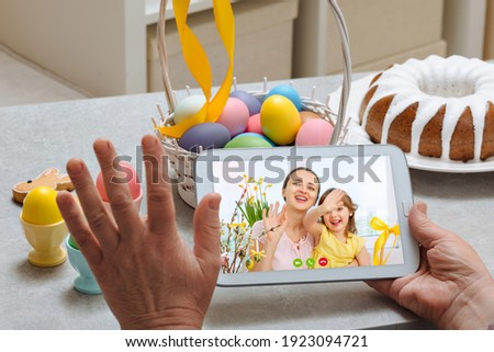 An elderly woman holds a digital tablet and yellow eggin her arms and talks to her granddaughters via video link during the Easter holiday.
