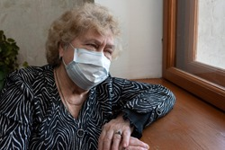 An elderly woman in a protective mask sits at home and looks out the window. Quarantine during a coronavirus pandemic.