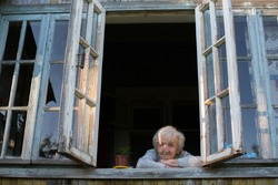 An elderly woman looks out of the window of a village house.