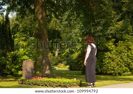 An elderly woman mourns at the cemetery about her dead husband deceased husband