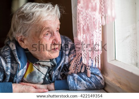 An elderly woman near the window. #422149354