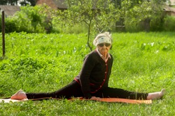 An elderly woman of 90 years old, with gray hair and a headband, makes a longitudinal split in the summer morning on a mat in the garden. Longevity concept. Copy space