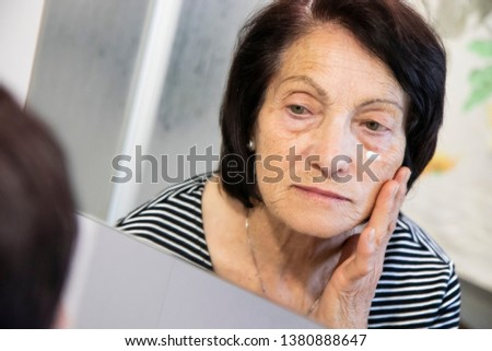 An elderly woman, old lady, looks in the mirror at her aged and wrinkled face, and rubs an anti-wrinkle cream. Dark circles, fatigue, old age, eye bags.