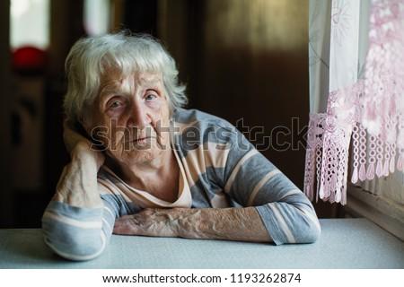 An elderly woman pensioner sits sadly near the window. Сток-фото ©